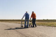 Two old friends walking on a country road, using wheeled walkers - UUF15529