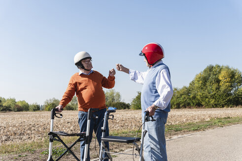 Two old friends wearing safety helmets, preparing for a wheeled walker race - UUF15535