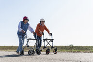 Two old friends wearing safety helmets, competing in a wheeled walker race - UUF15538