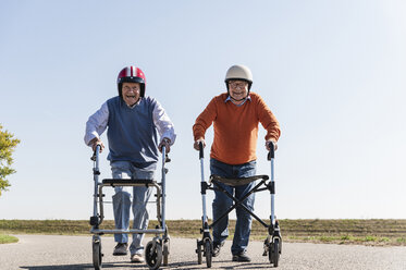Two old friends wearing safety helmets, competing in a wheeled walker race - UUF15541