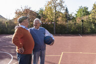 Two fit seniors having fun on a basketball field - UUF15547