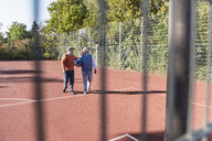 Two fit seniors having fun on a basketball field - UUF15550