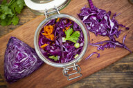 Homemade red cabbage, fermented, with chili, carrot and coriander, preserving jar on wood - LVF07486