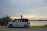 Woman on top of the van making a selfie at sunset on the lake - SKCF00538