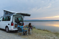 Couple having dinner an the camper at sunset on the lake - SKCF00541