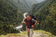 Male hiker with backpack standing on mountain at Sagarmatha National Park - CAVF49979