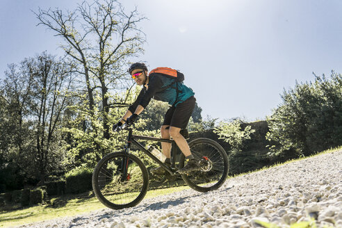 Full length of young man riding mountain bike at park during sunny day - CAVF49985