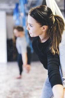 Friends practicing aerial yoga in gym - CAVF50000