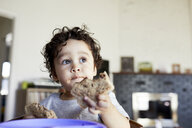 Close-up of cute thoughtful baby boy holding breads while looking away at home - CAVF50009