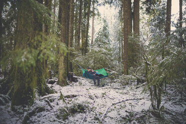 Couple resting in hammock amidst forest at Lynn Canyon Park during winter - CAVF50018