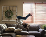 Full length of girl backflipping on couch at home - CAVF50033