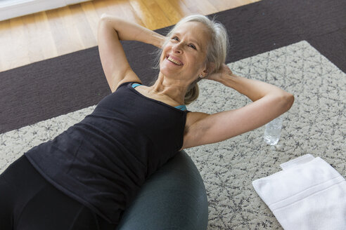 Smiling senior woman with hands behind head lying on fitness ball while exercising at home - CAVF50057