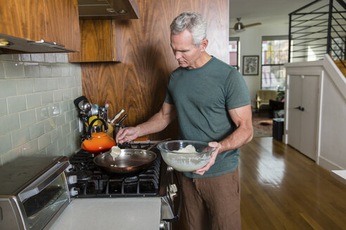 Mature man pouring batter in frying pan while cooking at home - CAVF50060