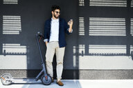 Smiling young man with electric scooter taking selfie with smartphone - BSZF00762