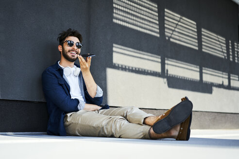 Portrait of relaxed young man sitting on the ground talking on mobile phone - BSZF00777
