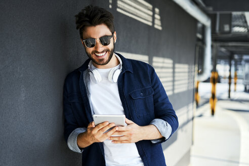 Portrait of smiling young man leaning against wall looking at digital tablet - BSZF00780
