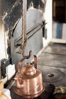 Copper kettle hanging on hook above hearth - PSIF00115