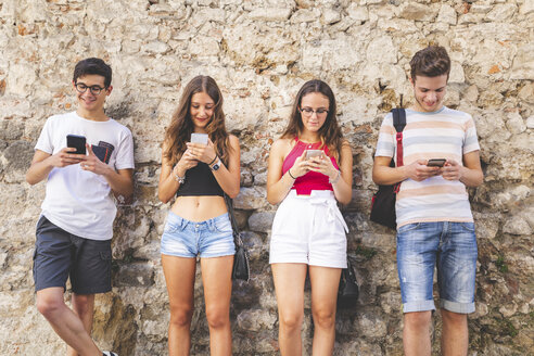 Group of friends standing at a wall using their cell phones - WPEF00920