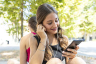 Two young women together at park listening to music - WPEF00926