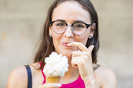 Portrait of smiling young woman eating ice cream - WPEF00932