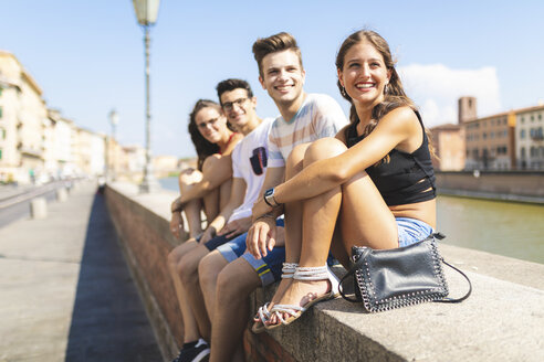 Italy, Pisa, group of four happy friends sitting on a wall along Arno river - WPEF00938