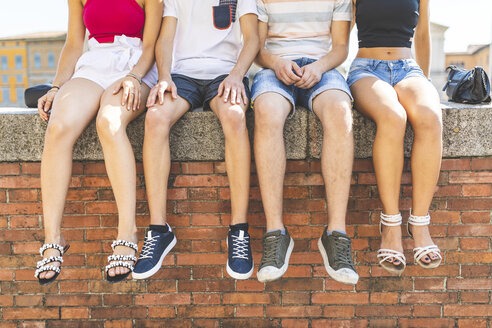 Legs of friends sitting together on a wall - WPEF00941