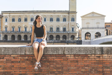 Italy, Pisa, young woman sitting on a wall in the city - WPEF00944