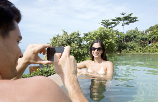 Young man photographing young woman in swimming pool by sea - LUXF01413