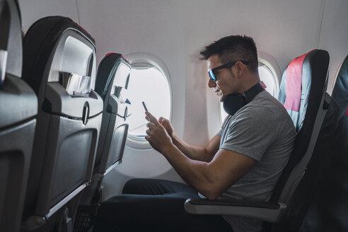 Man in airplane, using smartphone, headphones - KKAF02452