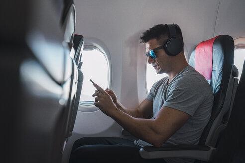 Man in airplane, using smartphone, headphones - KKAF02455