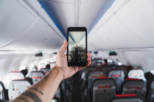 Airplane, man using smartphone, taking a picture interior - KKAF02467