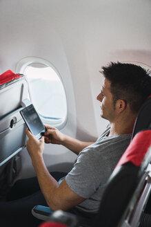 Man using ebook in airplane - KKAF02470