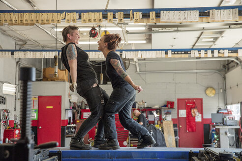 Side view of happy female mechanics dancing in auto repair shop - CAVF50113