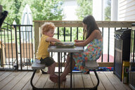 Side view of siblings with colorful crayons in box sitting on bench at porch - CAVF50182
