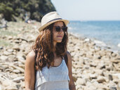 Woman wearing sunglasses and hat while standing at rocky beach against sky during sunny day - CAVF50185