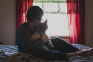 Boy embracing dog while sitting on bed at home - CAVF50188