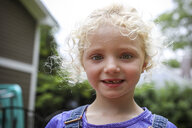 Close-up portrait of cute girl with messy blond hair standing against sky at yard - CAVF50203