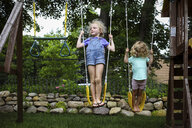 Full length of sisters playing on swings at playground - CAVF50209