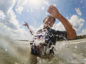 Low angle view of teenage boy swimming in sea against cloudy sky - CAVF50212