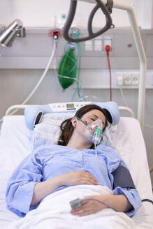 High angle view of female patient wearing oxygen mask while sleeping on bed in hospital - CAVF50221
