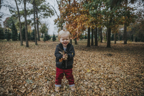 Portrait of happy baby boy playing with autumn leaves while standing at park - CAVF50227