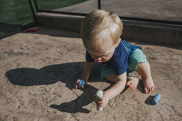 High angle view of baby boy holding chalks while sitting on footpath at playground - CAVF50230