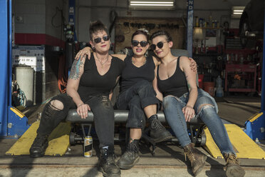 Full length of female mechanics wearing black sunglasses sitting side by side in auto repair shop - CAVF50233