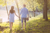 Rear view of couple holding hands while walking on grassy field at park - CAVF50245