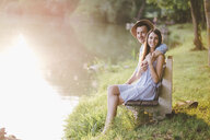 Portrait of couple sitting on bench by lake at park - CAVF50248