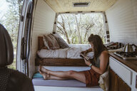 Side view of woman reading book while sitting on seat in motor home - CAVF50257