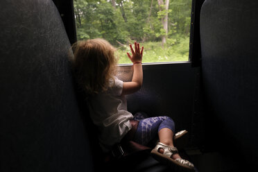 Side view of girl looking through window while traveling in bus - CAVF50299