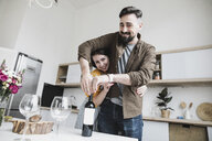 Portrait of happy couple with bottle of red wine in the kitchen - KMKF00574