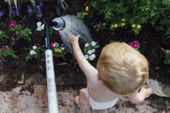Rear view of shirtless baby boy playing with water while standing by plants at yard - CAVF50310