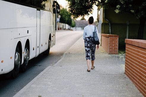 Rear view of woman walking on sidewalk by bus in city - CAVF50319